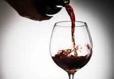 O vinho da uva derramou da garrafa no vidro de vinho do vidro Imagem de Stock