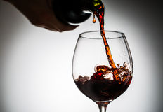 O vinho da uva derramou da garrafa no vidro de vinho do vidro Imagem de Stock Royalty Free
