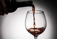 O vinho da uva derramou da garrafa no vidro de vinho do vidro Fotos de Stock Royalty Free
