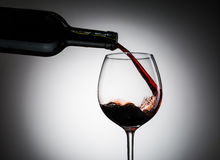O vinho da uva derramou da garrafa no vidro de vinho do vidro Foto de Stock