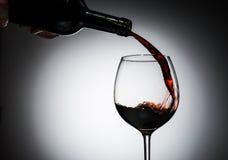 O vinho da uva derramou da garrafa no vidro de vinho do vidro Imagens de Stock Royalty Free