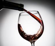 O vinho da uva derramou da garrafa no vidro de vinho do vidro Fotografia de Stock Royalty Free