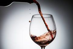 O vinho da uva derramou da garrafa no vidro de vinho do vidro Foto de Stock Royalty Free