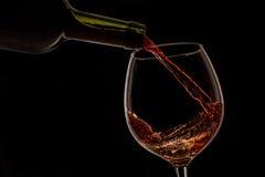 O vinho da uva derramou no vidro de vinho no fundo preto Imagem de Stock Royalty Free
