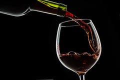 O vinho da uva derramou no vidro de vinho no fundo preto Imagem de Stock