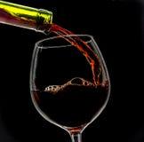 O vinho da uva derramou no vidro de vinho no fundo preto Fotos de Stock