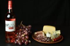 O vinho espanhol aumentou, uvas, queijo azul, prosciutto cortado e salame Imagens de Stock