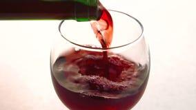 O vinho seco vermelho está sendo derramado ao vidro limpo cristal no restaurante vídeos de arquivo
