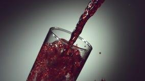 O vinho, suco de uva, suco da romã, suco da cereja é derramado em um vidro vídeos de arquivo