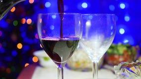 O vinho tinto é derramado em vidros No fundo, nas luzes do bokeh e nas festões do abeto do Natal Imagens de Stock