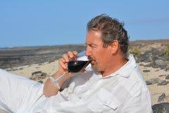 O vinho tinto bebendo do homem do vidro na praia Fotos de Stock Royalty Free