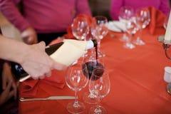 O vinho tinto de derramamento da mão da empregada de mesa no vidro para clientes Fotografia de Stock