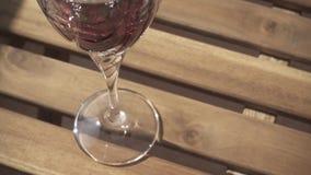 O vinho tinto do movimento lento é derramado em um vidro na tabela vídeos de arquivo