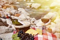 O vinho tinto, o queijo e as uvas serviram em um piquenique Imagens de Stock Royalty Free