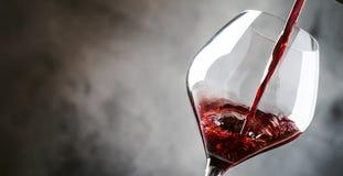 O vinho tinto seco francês, derrama no vidro, fundo cinzento, bandeira, foco seletivo fotografia de stock royalty free