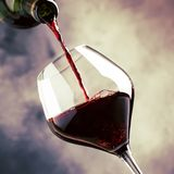 O vinho tinto seco francês, derrama no vidro, fundo cinzento, foco seletivo imagem de stock