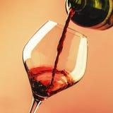 O vinho tinto seco franc?s, derrama no vidro, fundo cor-de-rosa na moda, espa?o para o texto, foco seletivo foto de stock