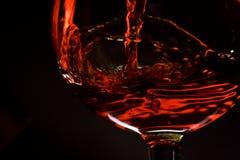 O vinho vermelho derrama em um vidro Foto de Stock