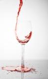 O vinho vermelho derrama no vidro Imagem de Stock Royalty Free