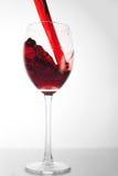 O vinho vermelho derrama no vidro Fotos de Stock Royalty Free