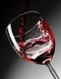 O vinho vermelho derramou no vidro Fotografia de Stock
