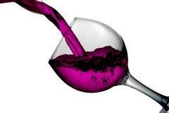 O vinho vermelho do deserto derramou dentro o vidro no fundo branco Foto de Stock