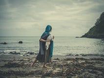 O vintage disparou da mulher na praia com bebê Foto de Stock Royalty Free