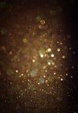O vintage do brilho ilumina o fundo ouro claro e preto defocused Imagens de Stock