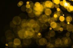 O vintage do brilho ilumina o fundo ouro escuro e preto defocuse imagens de stock