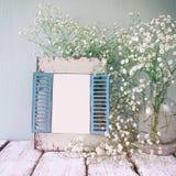 O vintage filtrou a imagem do quadro de madeira velho ao lado das flores brancas na tabela de madeira o molde, apronta-se para pô Imagens de Stock Royalty Free