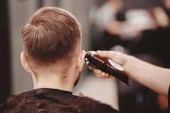 O vintage que tonifica, o barbeiro mestre faz o cabelo para equipar o moderno imagem de stock royalty free