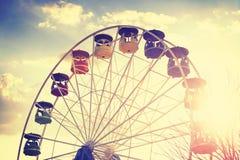 O vintage retro estilizou a imagem da roda de ferris no por do sol Fotos de Stock