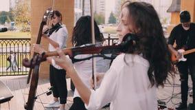O violinista de surpresa da menina joga expressively e belamente na fase com um grupo de rock vídeos de arquivo