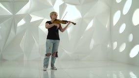 O violinista executa uma composição musical em um violino em um estúdio branco video estoque