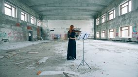 O violinista fêmea joga um violino em uma construção abandonada filme