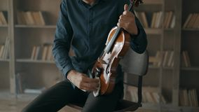 O violinista fricciona o violino da poeira com um pano Músico que importa-se com um instrumento musical com amor movimento 4k len filme