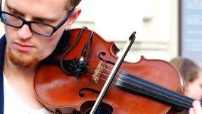 O violinista pressiona o violino a seu queixo e arranca as cordas com uma curva filme