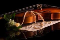 O violino encontra-se na tabela, ao lado das notas musicais isoladas no preto imagens de stock