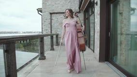 O violoncelista de sorriso anda no balcão e nos jogos no violoncelo vídeos de arquivo