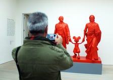 O visitante toma a foto do trabalho de arte em uma galeria Fotos de Stock