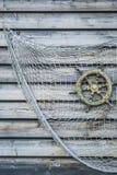 O volante de madeira do navio nostálgico com rede de pesca uniu t Fotos de Stock Royalty Free