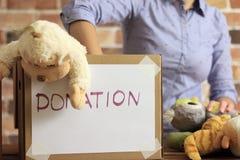 O voluntário está pondo brinquedos à caixa de cartão para a doação imagem de stock royalty free