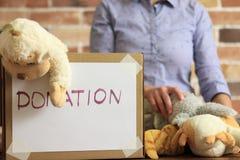 O voluntário está pondo brinquedos à caixa de cartão para a doação imagens de stock