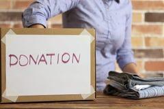 O voluntário está pondo a roupa à caixa de cartão para a doação fotografia de stock