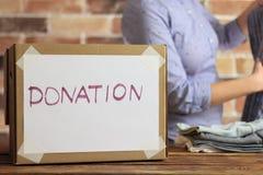 O voluntário está pondo a roupa à caixa de cartão para a doação foto de stock royalty free