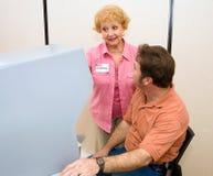 O voluntário explica a máquina de voto imagem de stock