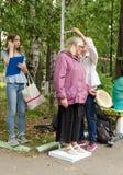 O voluntário fêmea mede o crescimento de uma mulher idosa imagens de stock royalty free