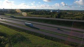 O voo aéreo acima do veículo branco monta na estrada com a área industrial Vista aérea com fundo do céu azul e das nuvens vídeos de arquivo
