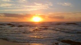 O voo aéreo do tiro lentamente da praia ao mar no por do sol em Portugal como ondas quebra no mar abaixo vídeos de arquivo