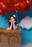 O voo bonito pequeno da menina no coração vermelho balloons o dia de Valentim Fotografia de Stock Royalty Free